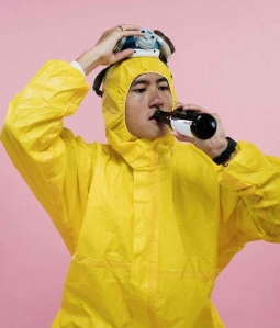 man in coveralls drinking beer
